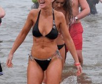 A woman laughs as she walks out of the sea in a bikini